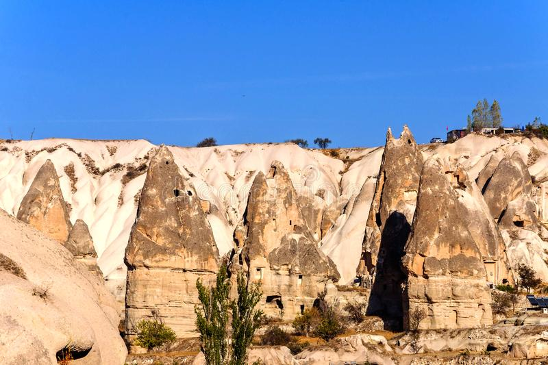 Cave towns in Volcanic rocks formation, Stone houses in Goreme, mountain landscape carved in tuff Cappadocia, Turkey royalty free stock image