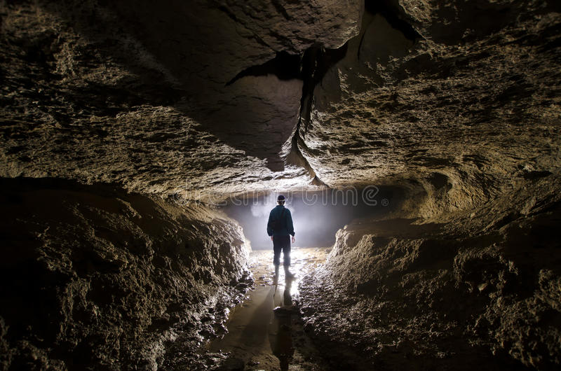 Cave underground with man speleologist and light at entrance. Man in cave underground with light at end of tunnel royalty free stock image