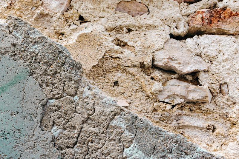 Caved old brick wall with peeled off plaster. White grey terracotta color shades with grungy rough texture. Cracked stained cement stock image