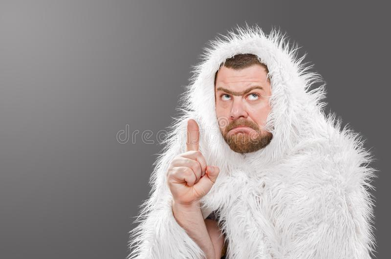 Caveman in animal skin on isolated background shows thumb up.  royalty free stock photo