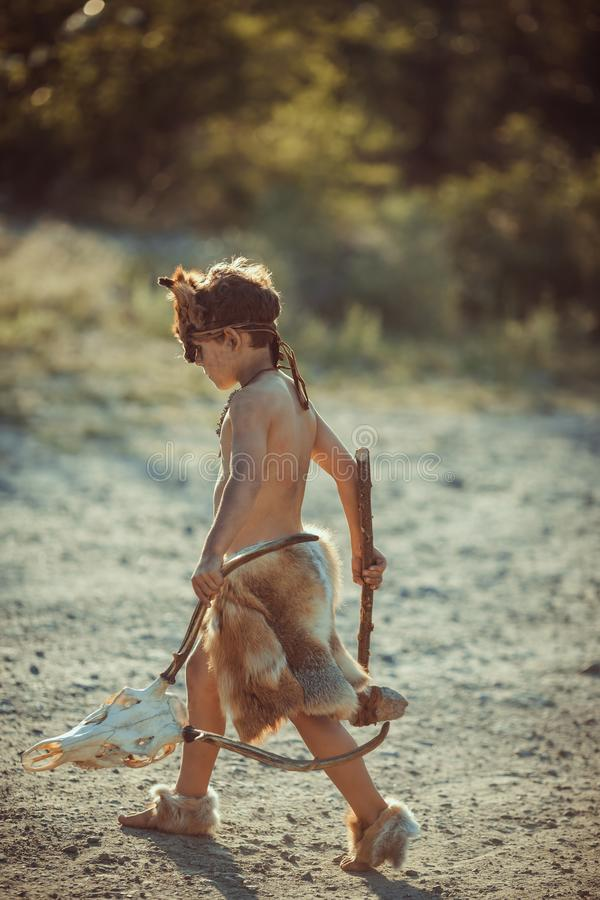 Caveman, manly boy with primitive weapon outdoors. Ancient prehistoric warrior. Angry caveman, manly boy with stone axe and animal skull. Prehistoric tribal boy royalty free stock image