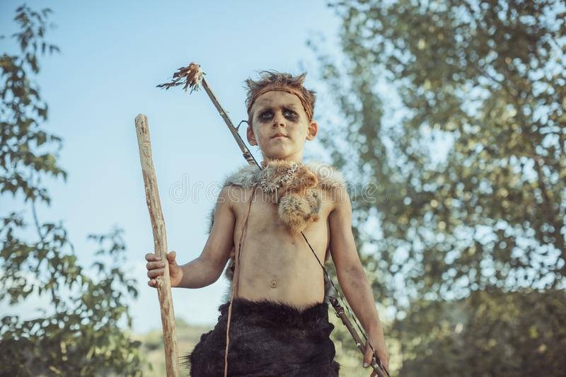 Caveman, manly boy with ancient primitive weapon hunting outdoors. Ancient warrior. Caveman, manly boy with staff and bow hunting near river. Prehistoric tribal royalty free stock photography