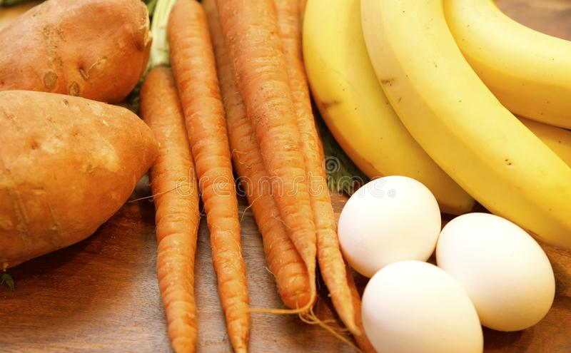 Paleo Diet Food. Elements of the Paleo Caveman diet, sweet potatoes, organic carrots, bananas and eggs royalty free stock photo