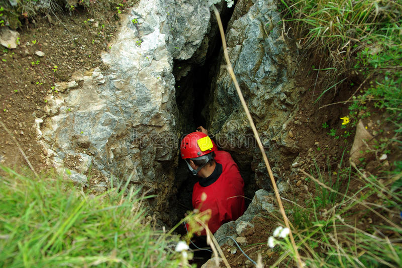 Caver descends in a cave royalty free stock image