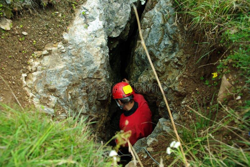 Caver desciende en una cueva imagen de archivo libre de regalías