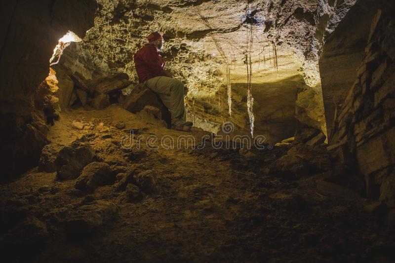 A caver explores a cave with a lantern. Odessa Catacombs, Ukraine royalty free stock images