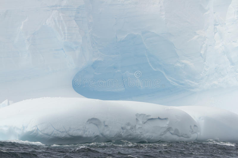 Cavern in blue glacial iceberg, Antarctica. Erosion cavern on blue glacial iceberg in Antarctica royalty free stock photo