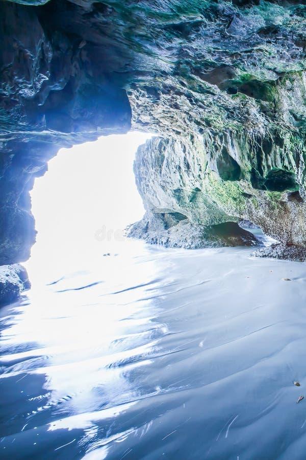 A caverna místico pelo mar, vista do interior da caverna que olha para fora, raio de sol brilha para baixo na praia da areia da o imagens de stock