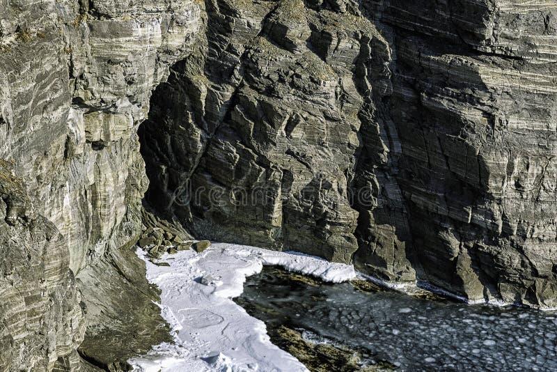 Caverna pequena em uma opinião do inverno da rocha com neve e gelo no mar imagem de stock royalty free