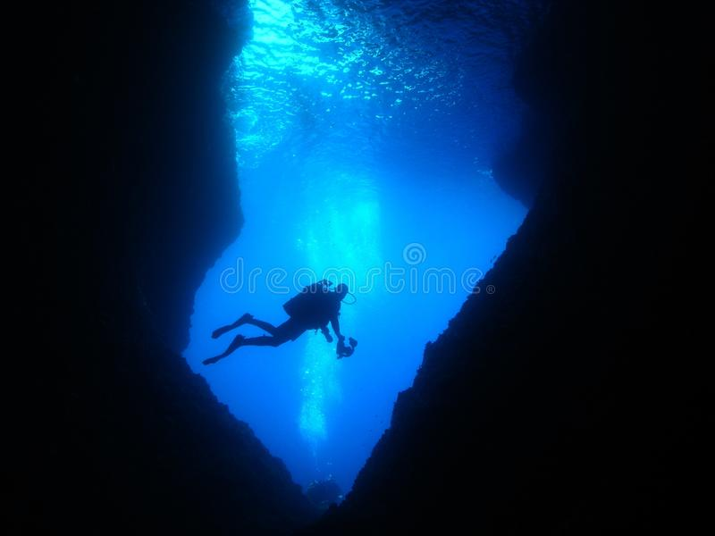 Caverna subacquea di immersione con bombole del fotografo dell'uomo fotografie stock libere da diritti