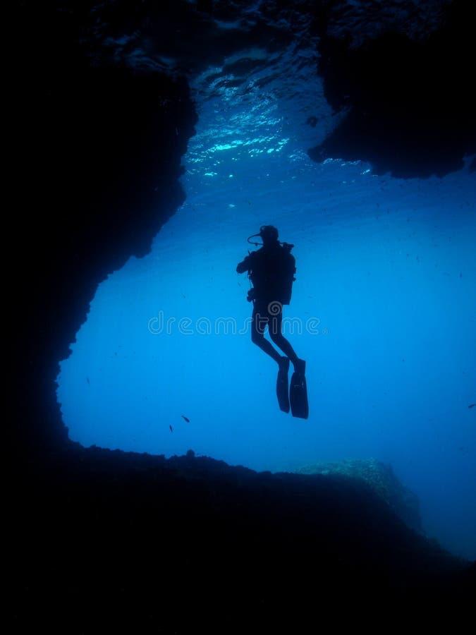 Caverna subaquática do mergulho autónomo do fotógrafo do homem imagem de stock royalty free