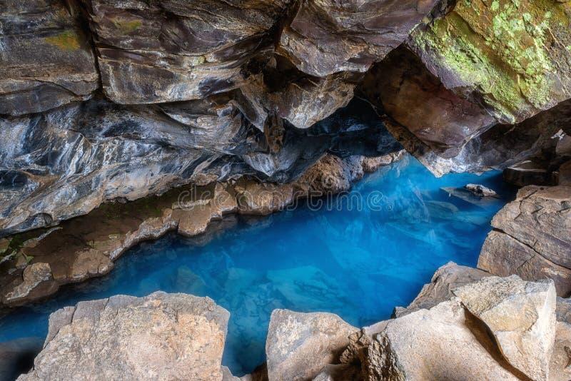 Caverne de Grjotagja en Islande avec de l'eau bleu stupéfiant chaud source thermale, petite caverne de lave photos libres de droits