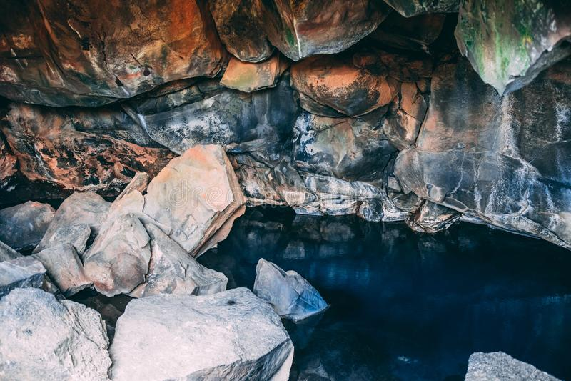 Caverne de Grotagja sur le nord de la région de l'Islande Myvatn avec l'intérieur clair bleu chaud de l'eau images stock