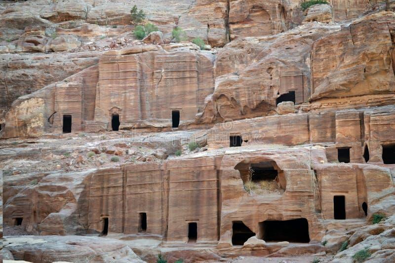 Cavernes dans PETRA, Jordanie - ville antique de Nabatean dans la roche naturelle rouge et avec les bédouins locaux, patrimoine m images libres de droits
