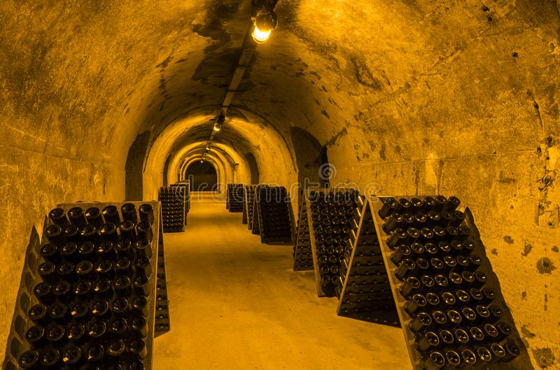 Caves Champagne House Taittinger in Reims. Reims, France - June 12, 2017: the caves of Champagne House Taittinger with old bottles Champagne in pupitres, France royalty free stock photography