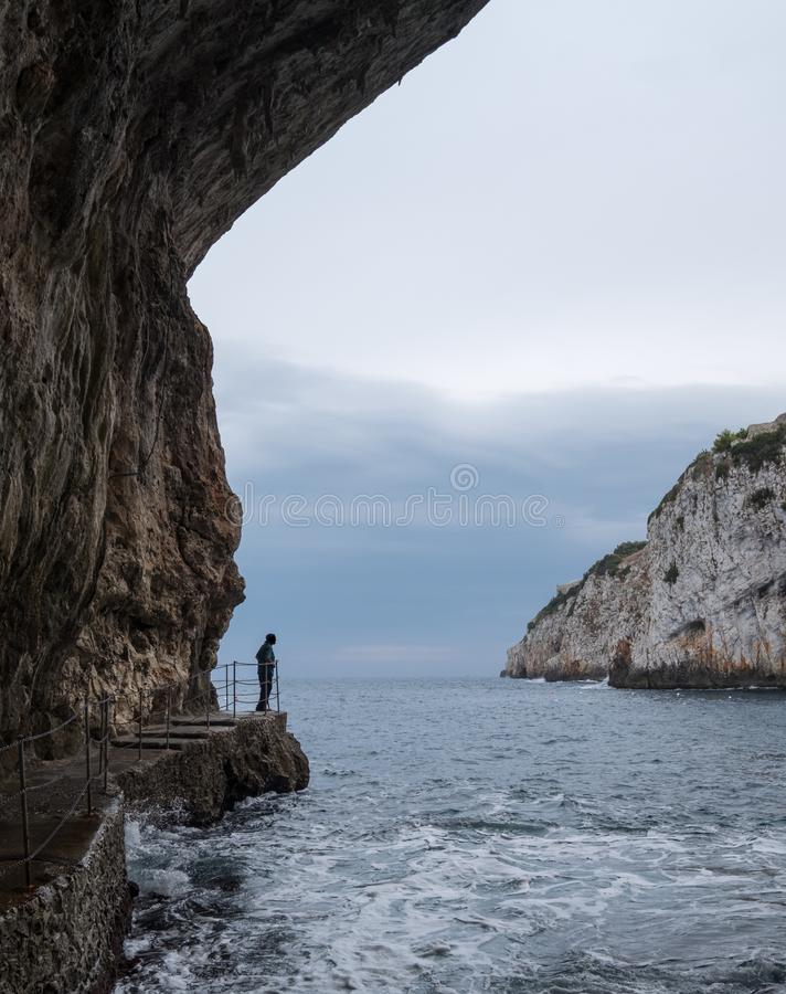 Caves of Zinzulusa, near Castro on the Salento Peninsula in Puglia, Italy. Person in silhouette stands on the gang plank. Caves of Zinzulusa, near Castro on the stock images