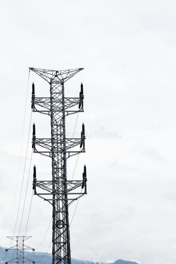 Cavi elettrici di alto potere del palo di corrente elettrica sul cielo bianco fotografia stock