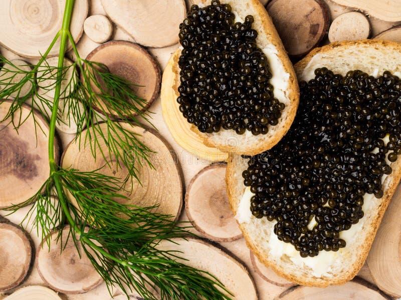 Caviale salato russo nero dello storione di Astrachan'su fondo di legno, fette di pane Spuntini e feste del lusso immagine stock libera da diritti