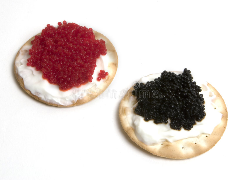 Caviar. Fancy black and red caviar with sour cream on top of crackers stock photos