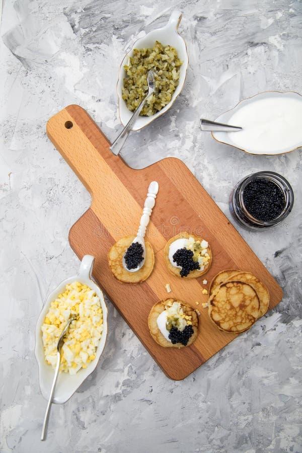 Caviar alemão preto na colher da pérola com blinis, creme de leite, apreciação do pepino e o ovo desbastado fotografia de stock