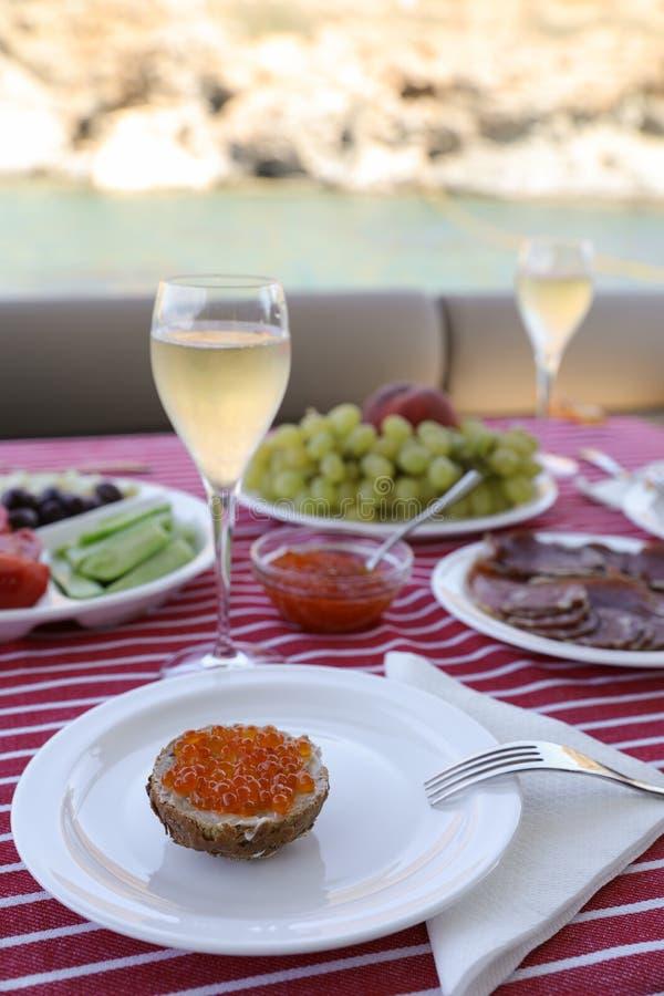 Caviar con champán y otros aperitivos durante vacaciones de verano por el yate imagenes de archivo