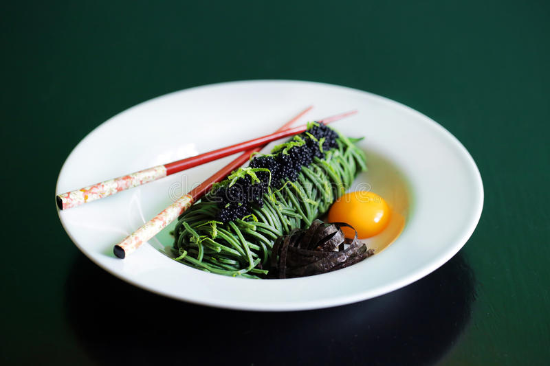 Caviar and green spirulina spaghetti noodles with egg yolk stock photos