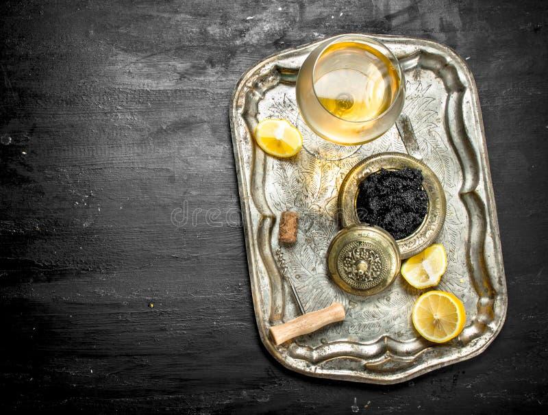 Caviar noir avec du vin blanc sur le vieux plateau photos libres de droits