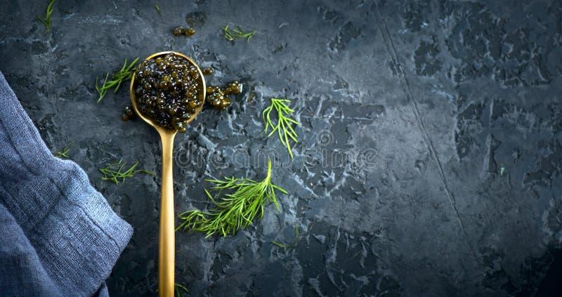 Caviar preto em uma colher no fundo escuro Close up natural do caviar do preto do esturjão delicatessen Vista superior fotos de stock royalty free