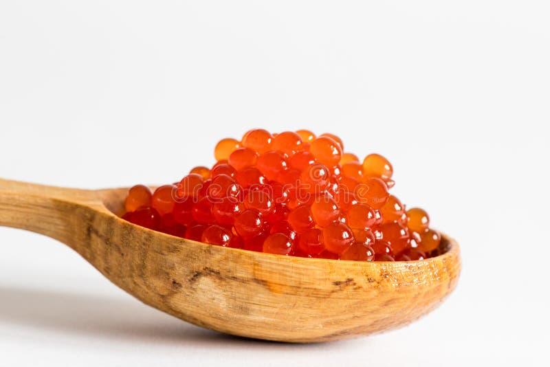 Caviar rojo en una cuchara en un fondo blanco imágenes de archivo libres de regalías