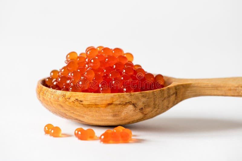 Caviar rojo en una cuchara en un fondo blanco foto de archivo