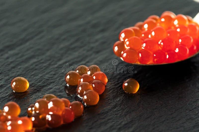 Caviar rojo en una cuchara en un fondo negro de la pizarra foto de archivo