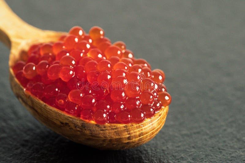 Caviar rojo en una cuchara en un fondo negro de la pizarra foto de archivo libre de regalías