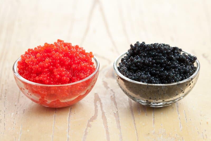 Caviar rojo y negro en tazón de fuente fotografía de archivo libre de regalías
