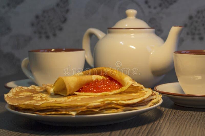 Caviar rouge et crêpes sur fond de théière photographie stock