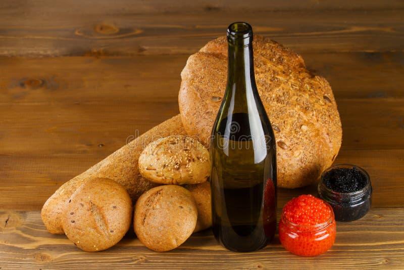 Caviar rouge et noir, vin blanc et pain sur la table images stock