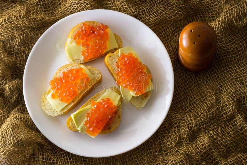 Caviar rouge sur le plan rapproché de pain et de beurre, quatre sandwichs du plat blanc Vue de ci-avant image stock