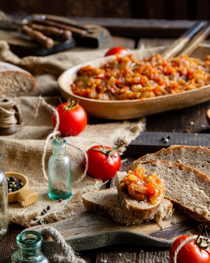 Caviar vegetal alaranjado saboroso caseiro, ratatouille ou ragu em fatias de pão e no prato de madeira oval na tabela marrom rúst imagens de stock