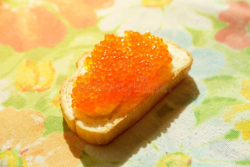 Caviar vermelho em um pão branco fotos de stock