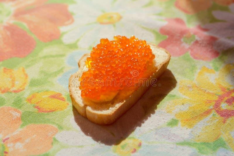 Caviar vermelho em um pão branco foto de stock