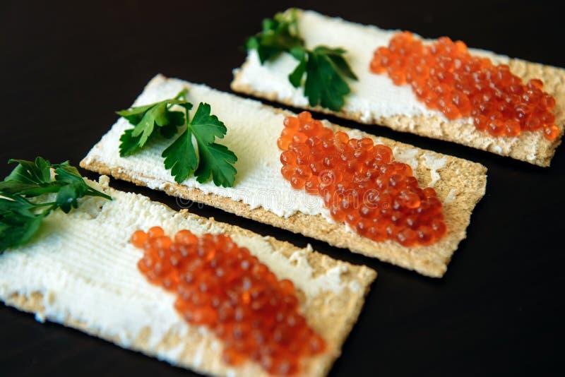 Caviar vermelho no p?o fri?vel com queijo creme e verde Alimento saud?vel Sanduíches com o caviar isolado no fundo preto fotografia de stock royalty free