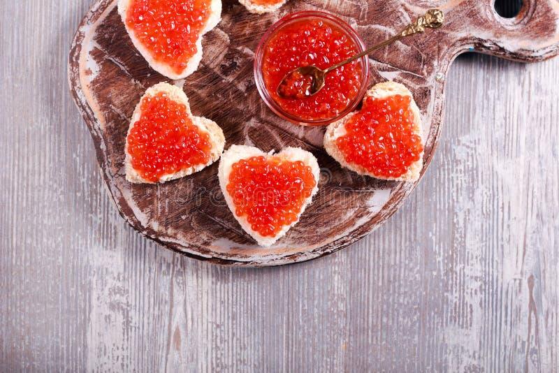Caviar vermelho sobre o pão da forma do coração imagens de stock royalty free