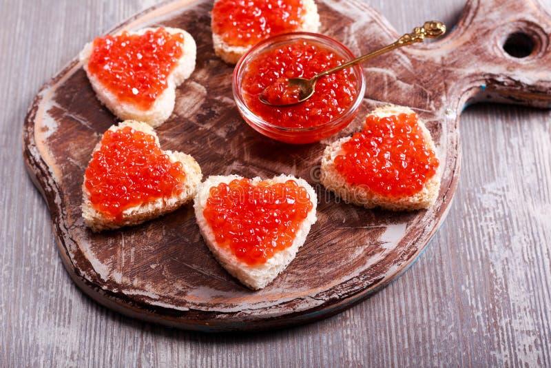 Caviar vermelho sobre o pão da forma do coração fotos de stock royalty free