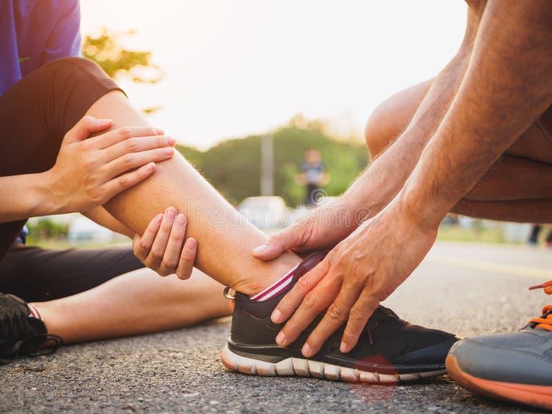 Caviglia storta Giovane donna che soffre da una ferita alla caviglia mentre immagine stock