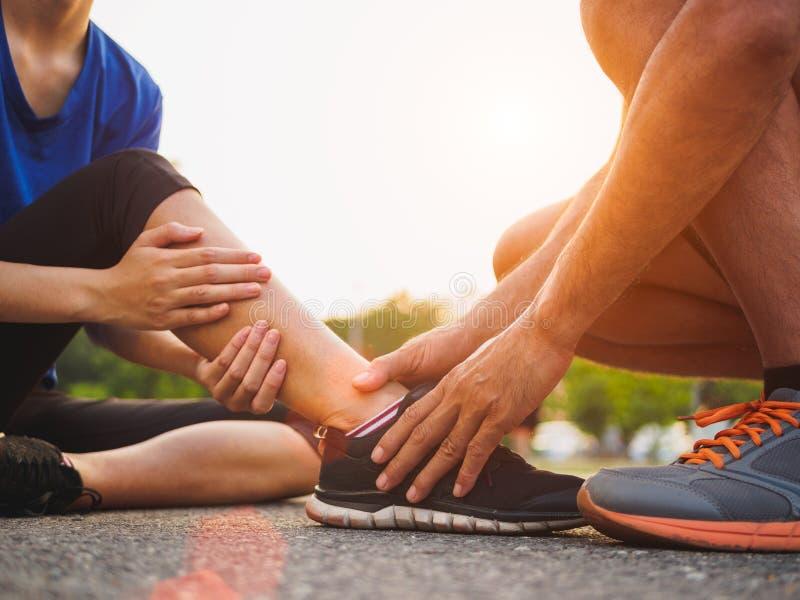 Caviglia storta Giovane donna che soffre da una ferita alla caviglia mentre fotografie stock libere da diritti