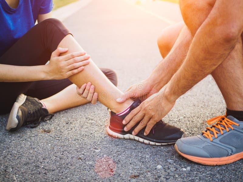 Caviglia storta Giovane donna che soffre da una ferita alla caviglia mentre fotografie stock