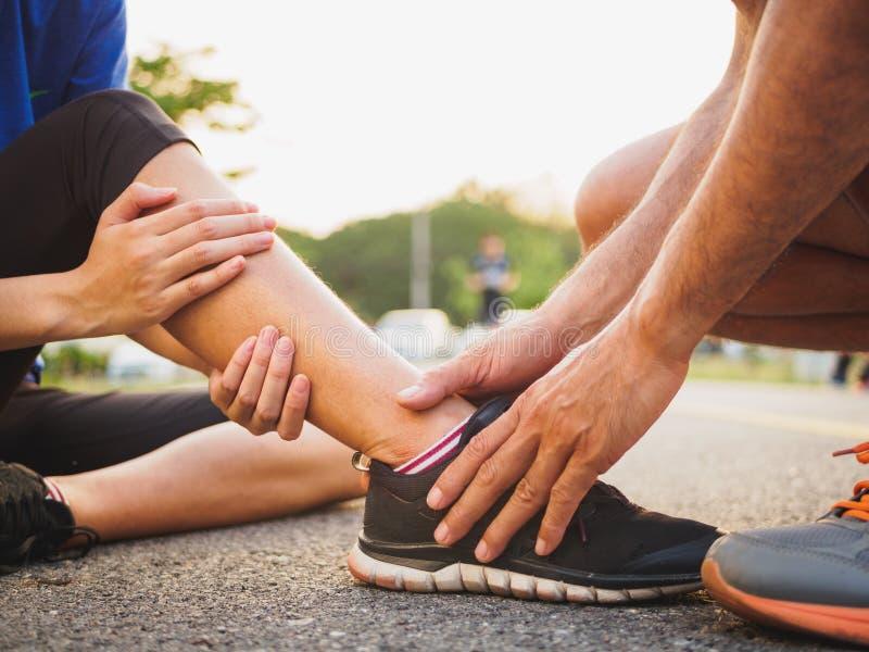 Caviglia storta Giovane donna che soffre da una ferita alla caviglia mentre immagini stock