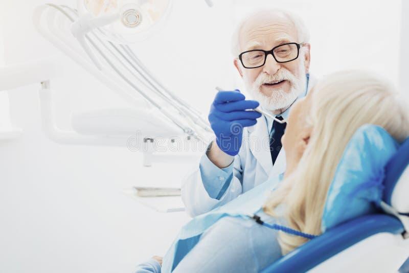 Cavité de bouche de examen inspirée de dentiste masculin photo stock