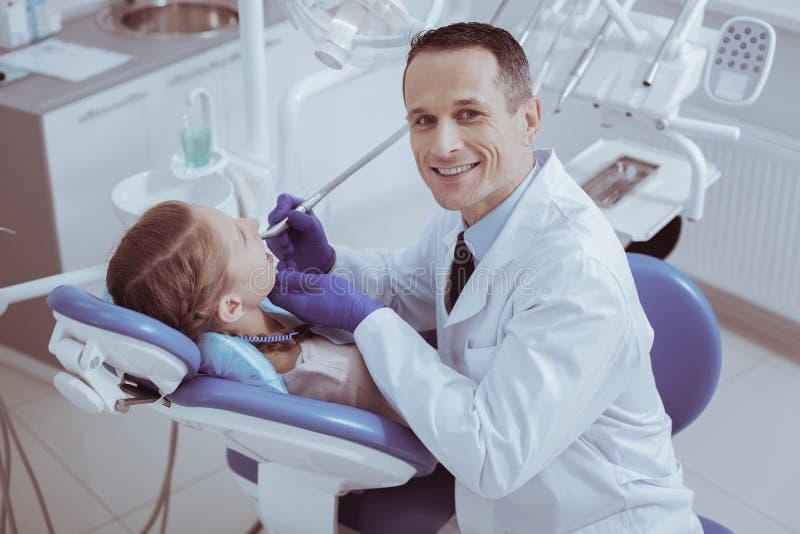 Cavités remplissantes d'heureux dentiste masculin images stock