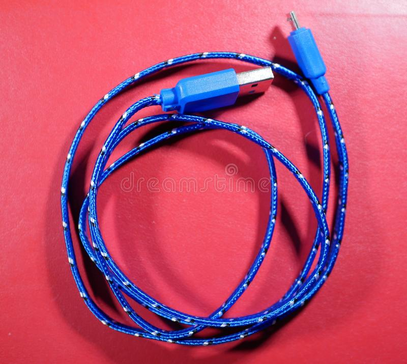Cavo di USB in treccia blu con i punti bianchi su fondo rosso fotografia stock