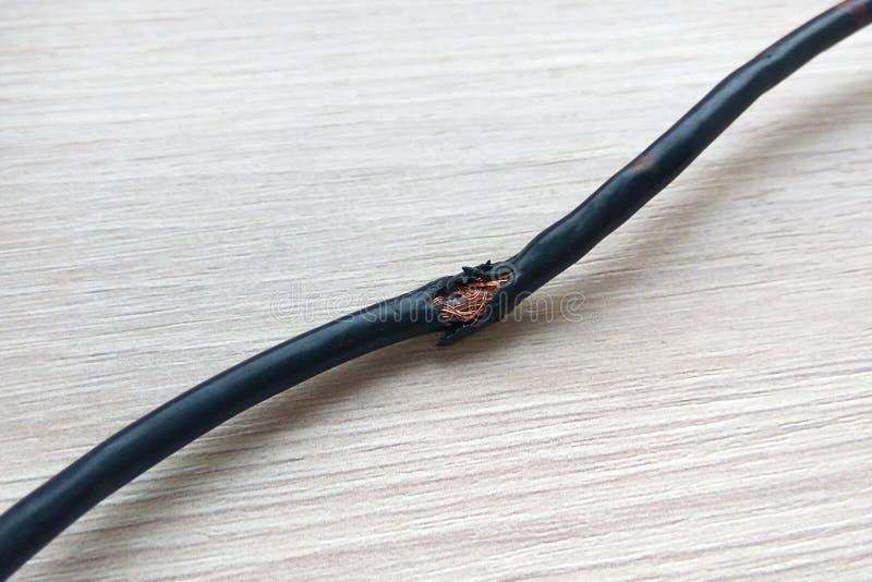Cavo elettrico nero nocivo sul fondo di legno del pavimento Cavo elettrico rotto pericoloso fotografia stock